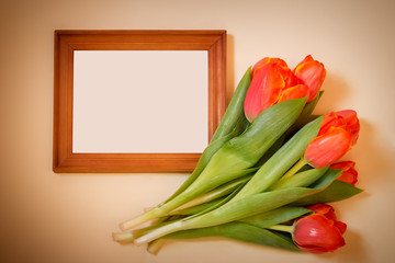 Tulips with blank picture frame on beige background