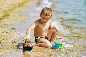 The boy plays with toys at sea . Cheerful child on a sea holiday