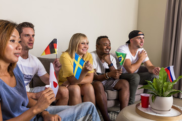 Group of young multinational sports fans cheering and watching TV