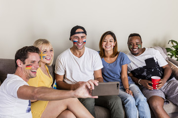 Multinational sports fans with facepainted flags laughing and taking selfie