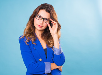 Happy business woman in eyeglasses looking at the camera over blue background