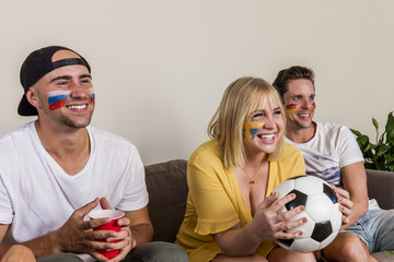 Multinational sports fans watching football on TV with cheer and excitement