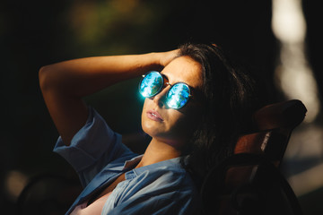 cute woman sitting on bench with fashionable round sunglasses.