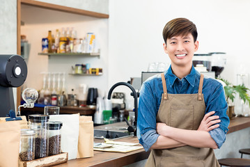 Cheerful young Asian man entrepreneur in coffee shop