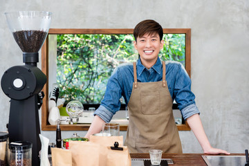 Smiling young Asian man entrepreneur at coffee shop counter bar