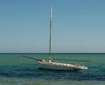A little old sailboat on a turquoise sea near Denham, Western Australia