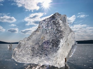 Beautiful transparent piece ice of Lake against sky and  bright sun.