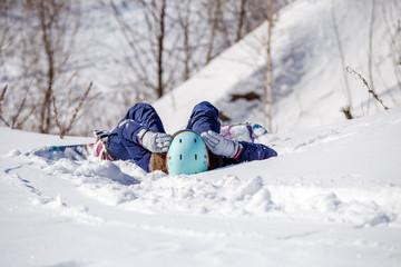 Portrait from back of athlete in helmet lying on snowy slope
