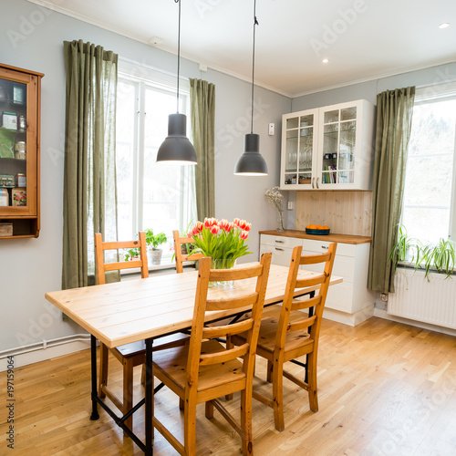 Kitchen Table In A Kitchen With Light Grey Walls And Green Curtains