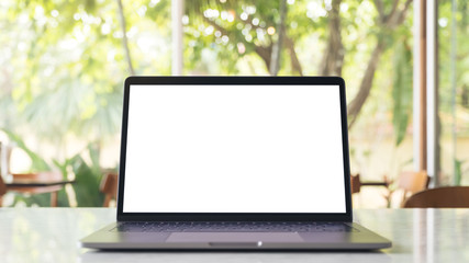 Mockup image of laptop with blank white desktop screen on marble table in modern cafe with nature background