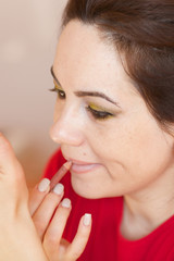 Young lady is applying make up on her face. Closeup