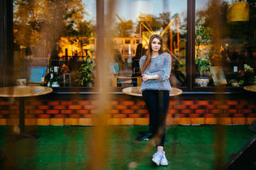 Young odd beautiful model girl with sensual pensive face posing for camera outdoor in front of shop showcase with abstract reflections in morning. Amazing teenager female with blue eyes mood portrait.