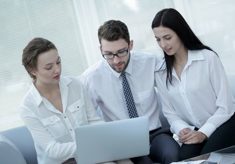 business team discussing information with laptop in office