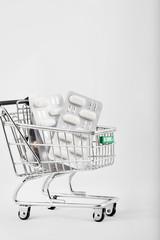 Pills in a mini shopping cart.