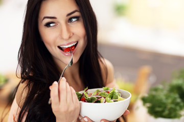 Happy woman preparing salad in modern kitchen