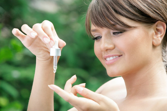 Young woman holding dropper with essential oil
