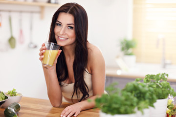 Fit smiling young woman with healthy juice in modern kitchen