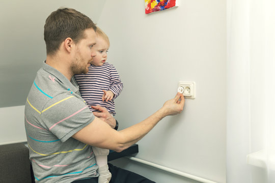 child safety at home. father takes care to protect kid from electrical injury