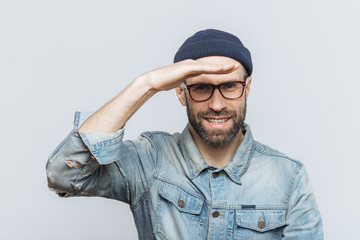 Cheerful unshaven middle aged male with thick stubble looks happily into distance, keeps hand near orehead, tries to see something, wears eyewear and denim jacket, isolated over grey background.