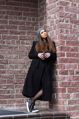 stylish young woman weared long black coat and gray knitted hat with coffe to go against brick wall