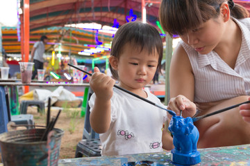 Asian cute girl baby and mother is painting colorful.
