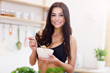 Fit smiling young woman with bowl of corn flakes in modern kitchen