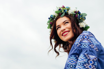 close-up of a beautiful girl with a wreath of flowers on the head who smiles sincerely