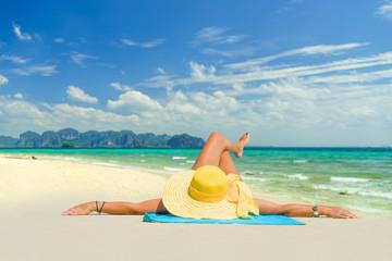 Woman in bikini wearing a yellow hat at tropical beach