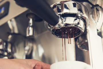 Coffee being brewed by the machine flowing into the cup