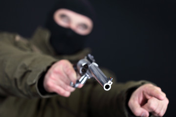 Robber with big revolver threats in front of black background