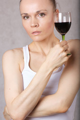 Young lady keeps a glass of red wine in her hand