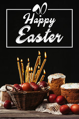 happy easter inscription in frame, burning candles, easter cakes and painted eggs on black