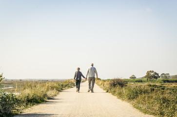 Elderly couple in love walking on a dust road, Portugal