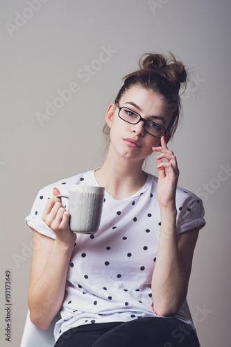 de4211bb329b Beautiful young teenage girl in eyeglasses holding a coffee mug. Studio  closeup portrait.