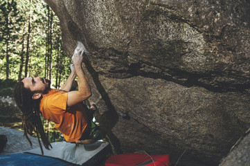 Man rock climber climbing overhanging boulder in scenic forest, Cavallers Dam, Spain