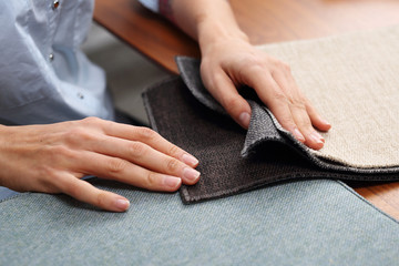 Fototapeta Zakupy sofy, wybór koloru obicia.  Kobieta ogląda kolory i wzory tkanin obiciowych. obraz