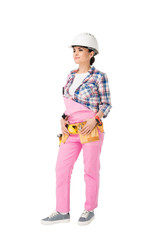 Attractive female builder in pink uniform with tool belt isolated on white