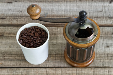 Coffee grinder with coffee beans in white cup on wood table.