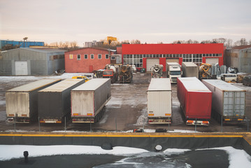 Industrial backyard with storehouse, trailers and trucks.