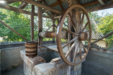 Old,traditional, wooden well with a large wheel, chain and bucket in the country side of Romania