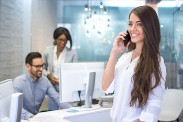 Smiling young business woman talking on mobile phone in office
