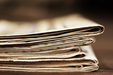 News - Pile of newspapers. Daily papers with articles and headlines stacked on the table. Actual information in press, fresh media. Folded tabloid pages on desk in office, data on paper. Side view