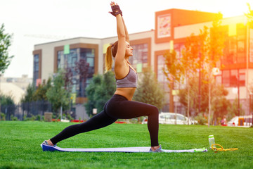 Beautiful attractive young woman stretching exercising in the park. Summer time. Health concept. Fitness concept.