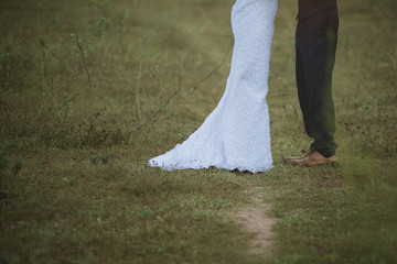 Closeup  of married couple holding hands. Bride and groom holding hands  stand in field.