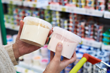 Buyer hands with plastic yogurt jars at grocery