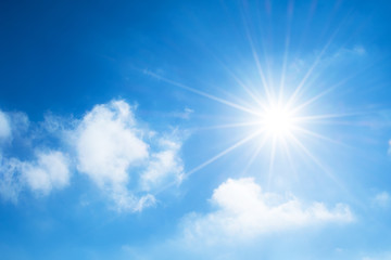 The sun with bright rays in the blue sky with white light clouds.