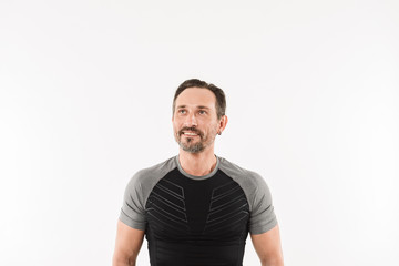 Portrait of masculine man 30s wearing sportswear looking upward on copyspace with smile and satisfied look after doing sports, isolated over white background