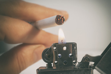 smoke and light cigarette from fire to gasoline lighter