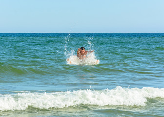 A sports man jumping over the sea waves in the black sea