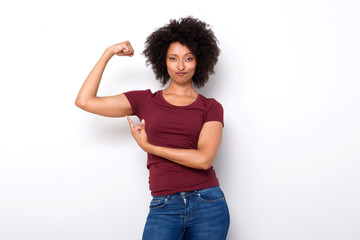 fit young african woman pointing at arm muscles on white background Wall mural